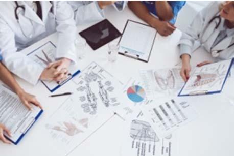Instantània on es veuen doctors i doctores en bata blanca amb actitud de comentar els informes que hi ha sobre d'una taula.